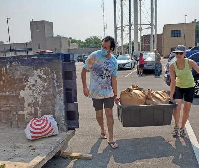 Joe Guerrero, left, and Alex Bass haul small yard trimmings to add to the compost collection. (EC)