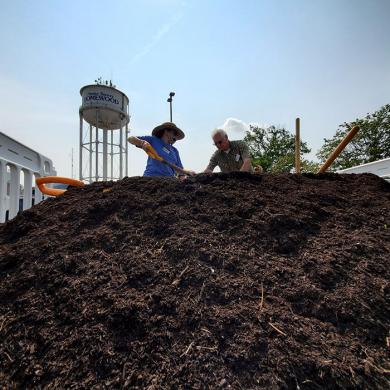 Marguerite McEnery, left, and Ken Cyrwus, master gardeners, help load buckets of compost for visitors to the event on July 24. (EC)