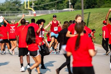 A runner makes his way through the H-F Marching Band line as they storm across, high-fiving runners on the way. (ABS)