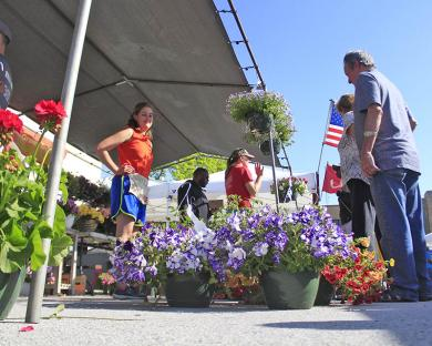 Amanda Wiegers helps customers shop for flowers at the Zeldenrust Farms booth.