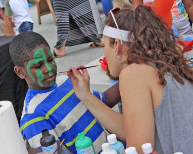 Darrick Jackson II of Glenwood gets a designed painted on his face by Savannah Reinhart at the John Harrell State Farm Insurance booth.