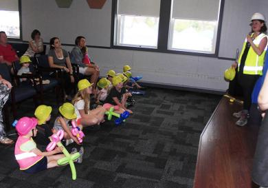 """Kids decked out in hard hats learn about building from """"Cool Women in Construction,"""" Kelsey Green and Christine Scully."""