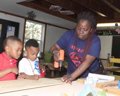 Lyza Howard of Country Club Hills helps young Alijah and Amaree Howard practice their building skills.