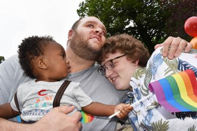 Homewood-Flossmoor High School teacher J.R. Rose gives a hug to former H-F student Callisto Wojcikowski of Homewood during the second annual Pride event in Flossmoor sponsored by Lighthouse, an LGBTQ support organization for youths and their families. Rose is holding his son, Rowan Willard-Rose.