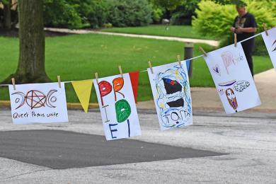 Posters made by visitors who attended the Pride event hang along Hutchison Road.