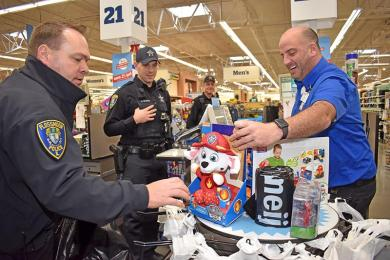 Eric Carney, far right, of Meijer Customer Service rings up thousands of dollars of toys the store donated to the Flossmoor Police Department. The department is donating all the toys to Toys For Tots. Helping to bag is Flossmoor police officer Tod Kamleiter as Officer Daniel Weaver (who did the shopping) looks on.