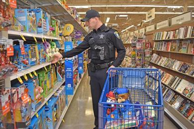Flossmoor police officer Daniel Weaver chooses some toddler toys at Meijer store in Flossmoor.