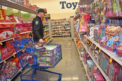 Flossmoor Police Officer Daniel Weaver chooses toys at the Meijer store in Flossmoor. Meijer donated funds for the officers to choose toys for needy children.