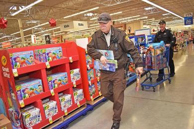 Dan Theisen, community service officer, chooses more toys as Sgt. Tim Filkins fills up his cart with toys.