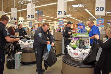 Flossmoor police officers check out and bag toys they chose at Meijer that were donated to Toys For Tots.