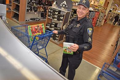 Sgt. Tim Filkins chooses children's movies at Meijer in Flossmoor. The store donated thousands of dollars for the police to choose toys for needy children.