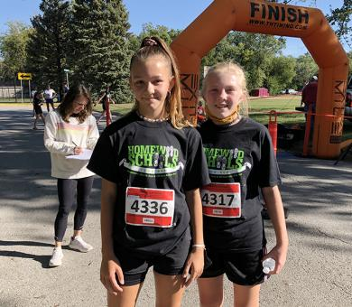 James Hart School cross-country team members Morgan Lawrence, left, and Addie Kempe, ran in the Fund Run. (MT)