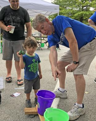 Everett Kinne, 2, got to enjoy a bucket toss game sponsored by Kirchner Vision Group in Homewood. Mike Nussbaum gives Everett some encouragement. (MT)