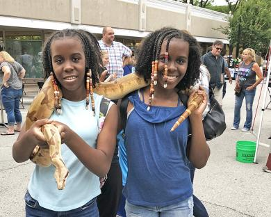 Sisters Isis, left, and Nasira McBride-Ali weren't afraid of the boa constrictor.  Daryl Herman walked around with the five-year-old pet giving kids a chance to pet the snake. (MT)