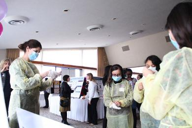 Jennifer LeRose, left, shows a group of girls how to put on protective garb used when treating infectious patients.