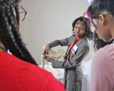 Daria Terrell uses a model to demonstrate what orthopedic surgeons do.