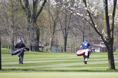 A twosome makes its way down a fairway at Ravisloe Country Club on Friday.