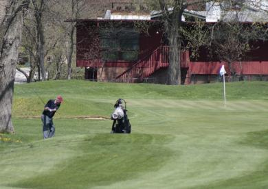 A golfer approaches a green at Ravisloe.