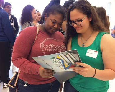 Alexa Sampson, left, and Kaitlyn Beverly enjoy looking at photos in a James Hart class yearbook.