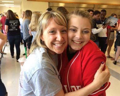 Eighth grade language arts teacher Eileen Wargo and James Hart graduate Maggie Robertson share a hug.