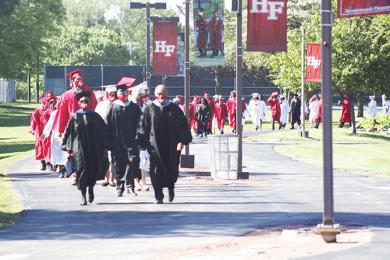 H-F Principal Jerry Anderson and Superintendent Von Mansfield lead students along the path from the South Building to the stadium for graduation ceremonies. (EC)