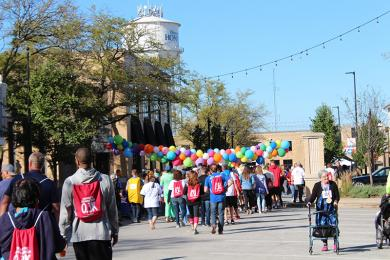 Race participants, many still chewing their mid-race doughnuts, saunter toward the finish line.