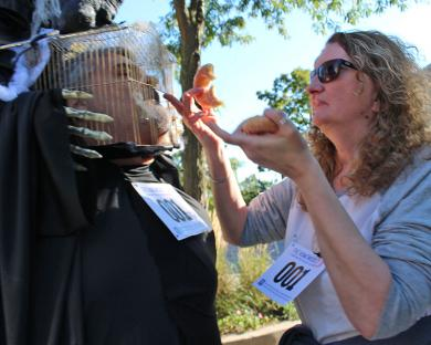 Chris Loudon's wife, Tracy, helps him eat a doughnut in spite of challenges presented by his costume.
