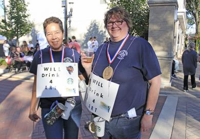 """Susan Gates, left, and Ginny Williamson sport """"Will drink 4 art"""" signs, plus tokens of each event sponsor."""