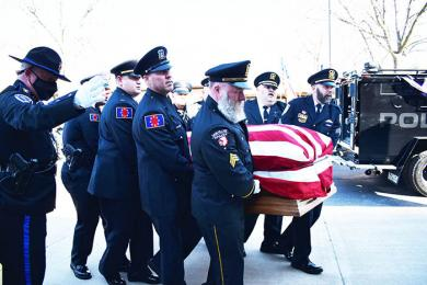 Officer in Charge Dan Watton from Rockford (left) guides police officers as they carry the body of Chicago Heights police officer Gary Hibbs. (MC)
