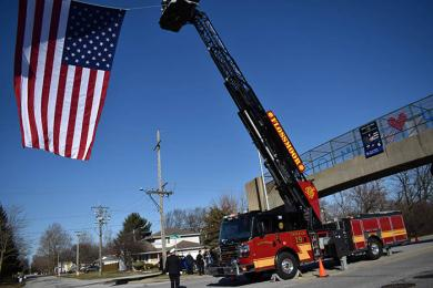 Flossmoor fire department engine 19 takes part in hanging an American flag in honor of fallen Chicago Heights officer Gary Hibbs. The flag was draped on Halsted Avenue during Hibbs' funeral. (MC)