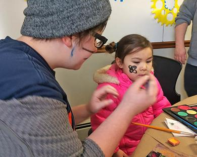 Charlotte McManus, a member of TALK, was a volunteer who painted a bee on the cheek of 3-year-old Emilia Leahy of Homewood. (MT)