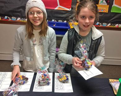 Volunteers Haley Maharry, left, and Teagan Meeks gave out passports to kids ready to do activities at Homewood's Chocolate Fest. (MT)