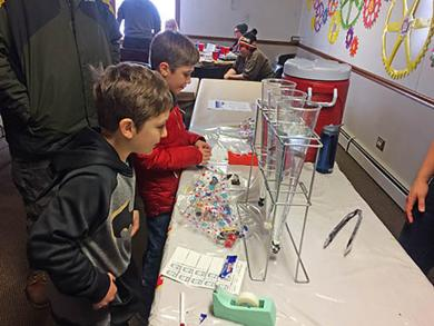Brothers Zak Gardner, 8 ( in red), and Drake Gardner, 7, select candies to drop into flutes of water to learn whether they will float. The experiment at the Homewood Science Center was part of Chocolate Fest. (MT)