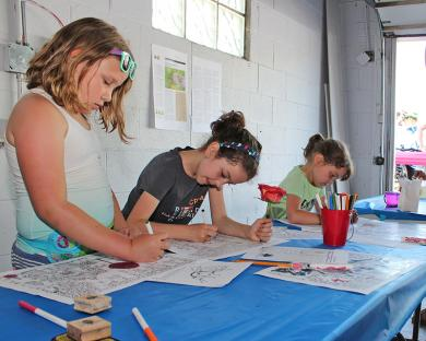 Youngsters do some coloring at the mini-Pop Up Science activity Saturday.
