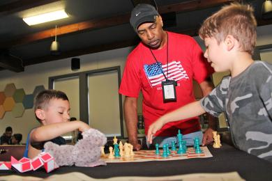 Cook Williams of Bright Knights provides advice to two young chess club members.