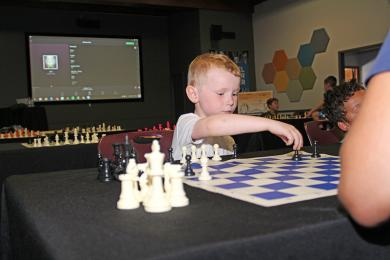 Duncan Thetford makes a move in his first-ever game of chess.