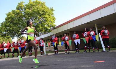 Homewood-Flossmoor High School cheer leaders offer encouragement to a runner.