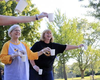 Joan Mahler, left, and Barb Radeke, teachers at Heather Hill School, hand water cups to runners at the corner of Lawrence Crescent and Scott Crescent.