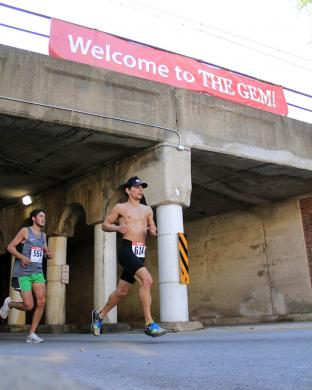 Runners near the front of the pack emerge from the Flossmoor Road viaduct to begin the last section of the course.