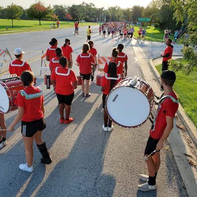 The H-F High drumline gives runners an early boost as they turn the corner onto Baythorne Drive,