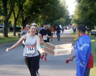 """A runner smiles as she slaps a """"speed boost"""" button on Veronica Rhodes' cardboard sign in the Flossmoor Hills neighborhood."""