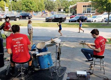 Sam Calhoon, right, and a group of musicians perform in the driveway of Michelle and Cameron Nelson to entertain runners.