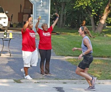"""Stephen and Donna Ramsey say """"cheers"""" with mimosas in hand to passing runners on Braeburn Avenue."""