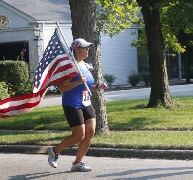 Sara Muncuia runs along Braeburn Avenue with an American flag. She and Calvin Jordan carried the flag to honor a servicewoman who was killed in Afghanistan. (EC)