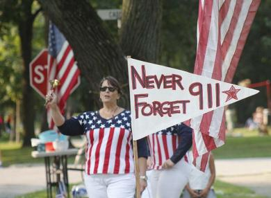 """Gigi Gummerson stands by a penant remind runners to """"never forget"""" the 9/11 tragedy. (EC)"""