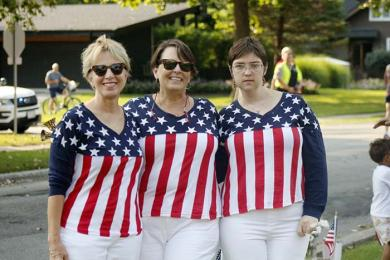 From left., Mary Beth Vieha, Gigi Gummerson and Gwen Gummerson pause from cheering runners in their patriotic outfits. (EC)