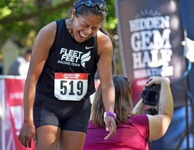 Columba Montes from Chicago gets emotional at the finish line after earning her best time, and coming in sixth among female runners. Montes, who emigrated from Mexico, said she began running when she came to the U.S.