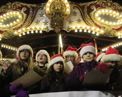 The Grand Prairie Children's Choir sings in front of the carousel at Holiday Lights in Homewood.