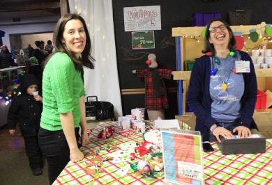 Science center staffers Kate Purvis, left, and Amy Eagle on duty in Santa's Workshop, where kids could make ornaments or candy trains.
