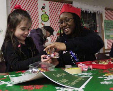 Homewood Science Center volunteer Kennedy Curtis, right, helps Pressley O'Brien with her candy train.